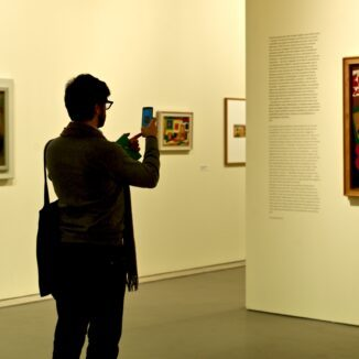 Man taking a picture of a painting in a museum