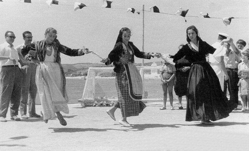 A black and white picture of three women dancing in Greek folk costume