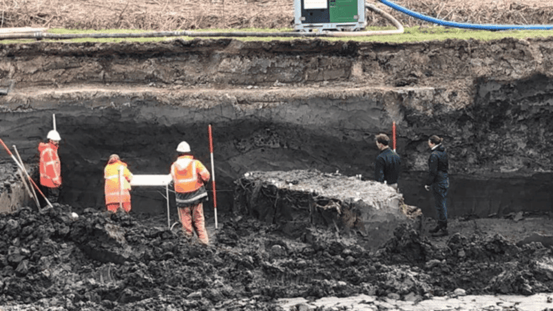 Archaeologists uncover a structure made of clay and wooden poles; some sort of dike, levee or embankment