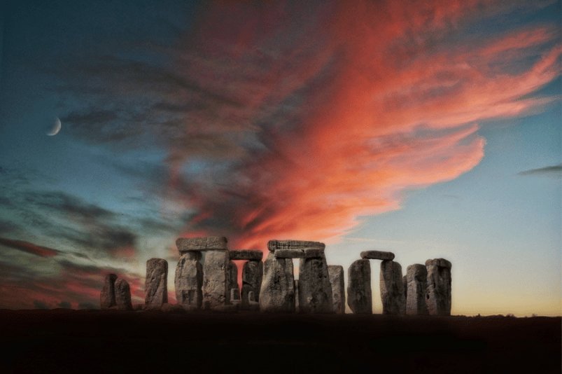 A picture of Stonehenge around dusk; clouds overhead are tinted red and on the left a crescent moon is visible.