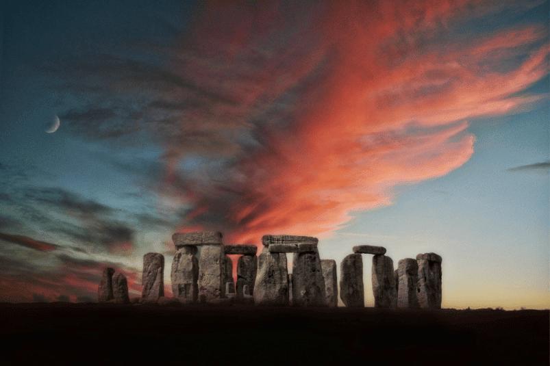 Ein Bild von Stonehenge in der Abenddämmerung; die Wolken darüber sind rot getönt und links ist eine Mondsichel zu sehen.